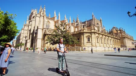 bazilika : SEVILLE, SPAIN - OCTOBER 2, 2019: Time lapse in crowded Constitution Avenue with a view on Gothic Cathedral of Saint Mary of the See and riding modern trams, on October 2 in Seville