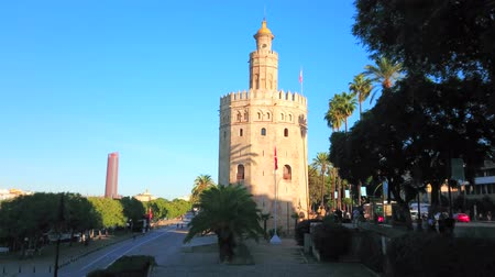 bank tower : SEVILLE, SPAIN - OCTOBER 2, 2019: The medieval Torre del Oro (Golden Tower) in morning sunlight and modern Torre Sevilla tower on background from the shady riverside park, on October 2 in Seville