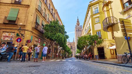andalucia : CORDOBA, SPAIN - SEPTEMBER 30, 2019: Fast traffic through the crowded tourist Calle Mateos Gago street, lined with historic mansions, with a view on Giralda bell tower, on September 30 in Cordoba