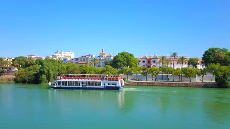 Андалусия : SEVILLE, SPAIN - OCTOBER 2, 2019: Pleasure boat trip along Guadalquivir river with a view on Maestranza bullring, greenery of Casco Antiguo district and Isabel II bridge, on October 2 in Seville