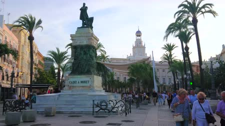 zegar : CADIZ, SPAIN - SEPTEMBER 19, 2019: The vibrant Plaza de San Juan de Dios with historical edifices, palm trees, town hall and the monument to Segismundo Moret, on September 19 in Cadiz