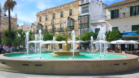 triângulo : SANLUCAR, SPAIN - SEPTEMBER 22, 2019: The crowded Plaza del Cabildo square boasts scenic fountain, shady trees, cozy cafes and fine townhouses, on September 22 in Sanlucar