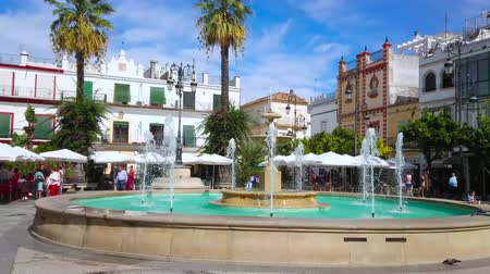 triângulo : SANLUCAR, SPAIN - SEPTEMBER 22, 2019: Ensemble of old Plaza del Cabildo square with stone fountain, greenery, outdoor cafes, historic townhouses and mansions, on September 22 in Sanlucar Stock Footage