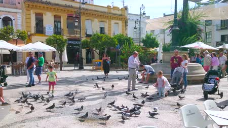 andalucia : SANLUCAR, SPAIN - SEPTEMBER 22, 2019: Families with kids feed and play with pigeons in Cabildo square, occupied with outdoor cafes and stores, on September 22 in Sanlucar