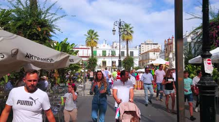 サンシェード : SANLUCAR, SPAIN - SEPTEMBER 22, 2019: The busy and crowded Plaza del Cabildo square is the central location of Old Town with historic townhouses, cafes and stores, on September 22 in Sanlucar 動画素材