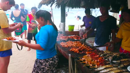 PHUKET, THAILAND - MAY 1, 2019: The open air kitchen of small beach cafe of Khai Nok island, cooks prepare chicken, fish, lobsters, shrimps and squids on grill, on May 1 on Phuket