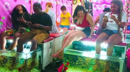 soyulması : PATONG, THAILAND - MAY 1, 2019: Tourists enjoy fish pedicure in spa of Banzaan Night Bazar, excited girl is scared of tickling and unusual feelings of skin peeling by doctor fishes, on May 1 in Patong