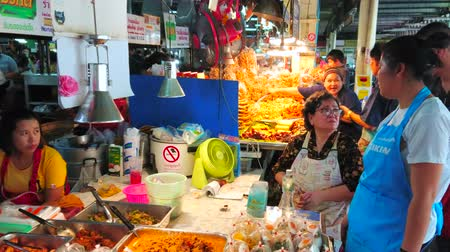 mercado : CHIANG MAI, THAILAND - MAY 4, 2019:  The vendors wait the clients in Tanin market stall of takeaway foods, offering dishes of traditional Thai cuisine, on May 4 in Chiang Mai