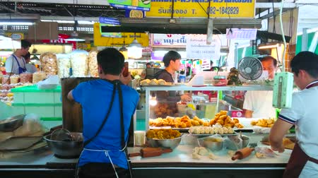 mercado : CHIANG MAI, THAILAND - MAY 4, 2019: The small kitchen in stall of Tanin market with cooks, preparing Thai deep fried curry puffs with different fillings, on May 4 in Chiang Mai