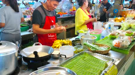 olej : CHIANG MAI, THAILAND - MAY 4, 2019: The cook in stall of Tanin market makes crispy rice crepe pancakes with banana filling, on May 4 in Chiang Mai Dostupné videozáznamy
