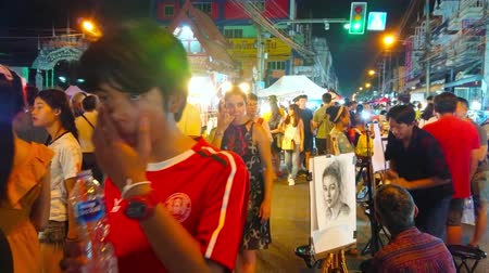 CHIANG MAI, THAILAND - MAY 4, 2019: The busy crowded Wualai walking street of Saturday Night Market with row of painters, offering quick sketch portrait drawing service, on May 4 in Chiang Mai Stock Footage