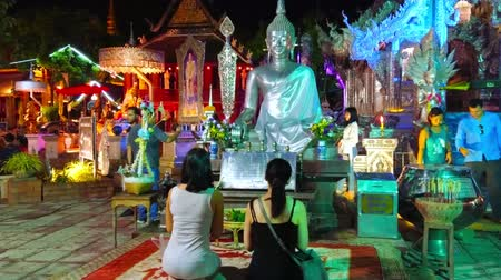 gravure : CHIANG MAI, THAILAND - MAY 4, 2019: The young female Buddhist devotees pray at the silver Buddha Image of Silver Temple (Wat Sri Suphan), on May 4 in Chiang Mai