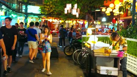 kluski : BANGKOK, THAILAND - APRIL 23, 2019: The noisy Khao San night market with crowds of walking tourists, bright lanterns and cart of pineapple vendor, on April 23 in Bangkok Wideo