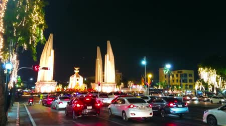 noc : BANGKOK, THAILAND - MAY 11, 2019: Many cars wait in queue at traffic light in Ratchadamnoen Avenue with a view on Democracy Monument in bright evening lights, on May 11 in Bangkok Wideo