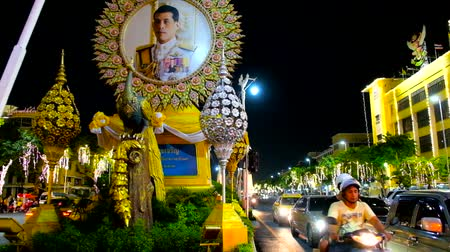 украшенный : BANGKOK, THAILAND - APRIL 24, 2019: The evening busy Ratchadamnoen Avenue is decorated with flags and portraits of the King Rama X due to the coronation ceremony, on April 24 in Bangkok