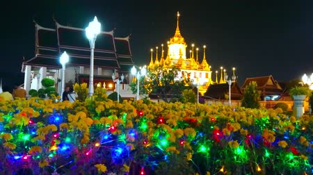 semt : BANGKOK, THAILAND - MAY 11, 2019: The colorful lights decorate the flower bed of Mahajetsadabadin park, Wat Ratchanatdaram complex, Bangkok, Thailand, on May 11 in Bangkok Stok Video