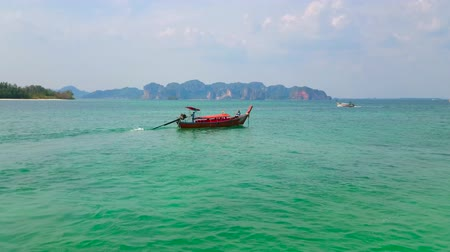 indianin : AO NANG, THAILAND - APRIL 26, 2019: The fast longtail boats float along the coast of Ko Poda Nok (Chicken) Island  - popular tourist destination, on April 26 in Ao Nang