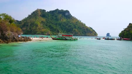 indianin : AO NANG, THAILAND - APRIL 26, 2019: Narrow sand spit between Koh Mor and Koh Tup Islands with moored tourist ships, holidaymakers and Ko Poda Nok (Chicken) Island on background, on April 26 in Ao Nang
