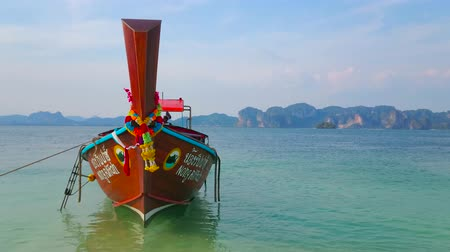 siamês : AO NANG, THAILAND - APRIL 26, 2019: The scenic wooden longtail boat is moored at the shore of Ko Poda Nok (Chicken) Island and rocking on the gentle tidal waves of Andaman sea, on April 26 in Ao Nang Stock Footage
