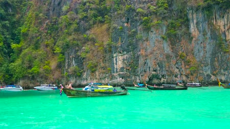 sziget : PHIPHI LEH, THAILAND - APRIL 27, 2019: Traditional longtail boats and tourist yachts float along the rocks of Phi Phi Leh Island through the emerald waters of Pileh Bay, on April 27 in PhiPhi Leh