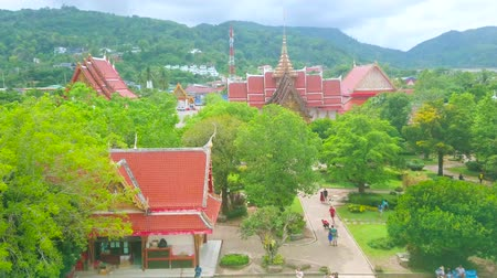 CHALONG, THAILAND - APRIL 30, 2019: The view from Wat Chalong Pagoda on the pyathat roofs and ornate details of shrines and Ubosot, hidden among the lush tropical greenery, on April 30 in Chalong