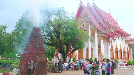 turisták : CHALONG, THAILAND - APRIL 30, 2019: The group of tourists has gathered at the brick firecracker pagoda of Wat Chalong temple and watches the loud firecracker show, on April 30 in Chalong