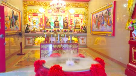 dekorasyon : BANGKOK, THAILAND - APRIL 15, 2019: The prayer hall of Chao Por Khao Tok Chinese Shrine with colorful Altar and small steam fountain in the middle, on April 15 in Bangkok Stok Video