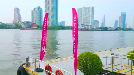 indochina : BANGKOK, THAILAND - APRIL 15, 2019: The pier of Asiatique Riverfront shopping center with colored flags and a view on modern high rises of business district, on April 15 in Bangkok Stock Footage