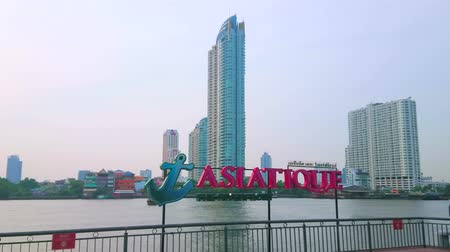 semt : BANGKOK, THAILAND - APRIL 15, 2019: The large sighnboard of the Asiatique Riverfront shopping center with Chao Phraya river and glass skyscrapers on the background, on April 15 in Bangkok