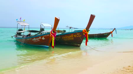indianin : AO NANG, THAILAND - APRIL 27, 2019: Bamboo Island is popular tourist destination, traditional longtail boats often bring here holidaymakers to  swim and relax on Bamboo beach, on April 27 in Ao Nang Wideo