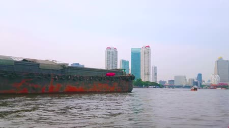 crepúsculo : BANGKOK, THAILAND - APRIL 15, 2019: The old wooden barge slowly floats along the Chao Phraya river with modern glass skyscrapers on the background, on April 15 in Bangkok