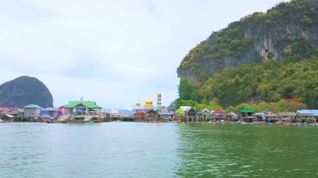 sziget : KO PANYI, THAILAND - APRIL 28, 2019: The speedboat trip along traditional floating Muslim village of Ko Panyi (Koh Panyee) with colorful stilt housing, mosque and moored boats, on April 28 in Ko Panyi