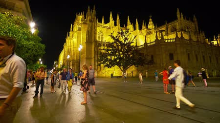 bazilika : SEVILLE, SPAIN - OCTOBER 1, 2019: Bright evening illumination of Seville Cathedral with crowd of people, walking along Constitution Avenue, on October 1 in Seville