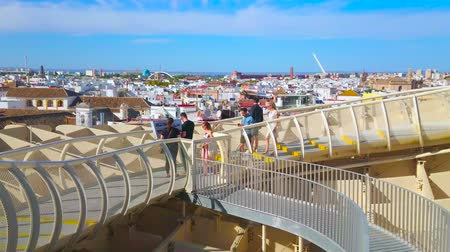 Андалусия : SEVILLE, SPAIN - OCTOBER 1, 2019: People enjoy the cityscape with town roofs from the panoramic terrace of Metropol Parasol, observing white Barqueta and Alamillo bridges, on October 1 in Seville
