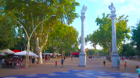 andalucia : SEVILLE, SPAIN - OCTOBER 1, 2019: The Lion columns in Alameda de Hercules garden square with spread white poplar trees and many outdoor cafes under the sunshades, on October 1 in Seville