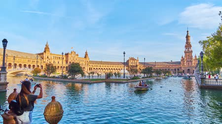 espana : SEVILLE, SPAIN - OCTOBER 2, 2019: Timelapse of Andalusian style Plaza de Espana (Spain Square) with canal, full of boats, fountain and stinning architecture, on October 2 in Seville
