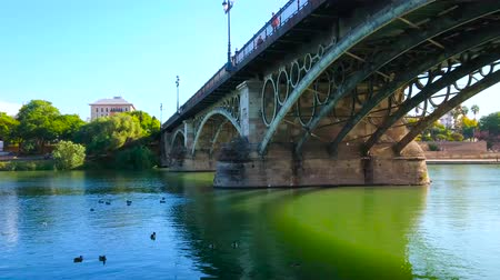 паром : SEVILLE, SPAIN - OCTOBER 2, 2019: The view on arched Isabel II bridge across Guadalquivir river and lush greenery on the opposite bank from embankment of Triana district, on October 2 in Seville