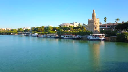 Андалусия : SEVILLE, SPAIN - OCTOBER 2, 2019: Line of moored tourist ships at the bank of emerald Guadalquivir river with a view on Casco Antiguo district and Torre del Oro (Golden Tower), on October 2 in Seville