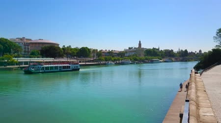 паром : SEVILLE, SPAIN - OCTOBER 2, 2019: The tourist ships, floating through the Guadalquivir river with a view on Casco Antiguo district and Torre del Oro (Golden Tower), on October 2 in Seville
