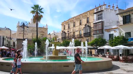 украшенный : SANLUCAR, SPAIN - SEPTEMBER 22, 2019: The crowded Plaza del Cabildo square, decorated with scenic fountain, is lined with popular tourist restaurants and old townhouses, on September 22 in Sanlucar