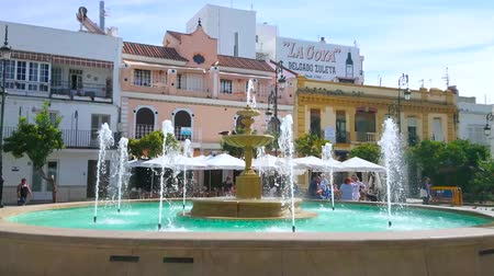 triângulo : SANLUCAR, SPAIN - SEPTEMBER 22, 2019: People walk the Plaza del Cabildo square with old fountain, cozy cafes and bars, historic edifices, on September 22 in Sanlucar Stock Footage