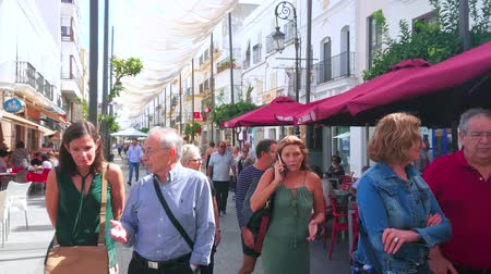 markiza : SANLUCAR, SPAIN - SEPTEMBER 22, 2019: The vibrant life in Calle Ancha street, full of fashion stores, cafes, restaurants and souvenir shops, attracting tourists, on September 22 in Sanlucar