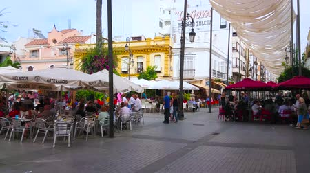 Андалусия : SANLUCAR, SPAIN - SEPTEMBER 22, 2019: The crowded outdoor terraces of popular restaurants in shopping Calle Ancha street, on September 22 in Sanlucar Стоковые видеозаписи