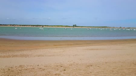 Panorama of Calzada beach with many moored boats, rocking on waters of Guadalquivir river, Sanlucar, Spain