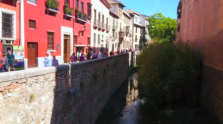 semt : GRANADA, SPAIN - SEPTEMBER 25, 2019: Walk the medieval stone embankment of Darro river, named Carrera del Darro street, located in Albaicin district of Old Town, on September 25 in Granada