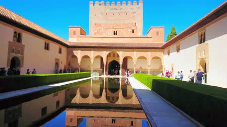 kolumna : GRANADA, SPAIN - SEPTEMBER 25, 2019: The medieval Court of Myrtles (Nasrid Palace, Alhambra) with Comares Tower and palace arcade, reflected in mirror pond, on September 25 in Granada