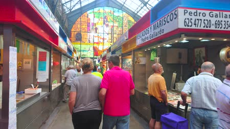 bakkaliye : MALAGA, SPAIN - SEPTEMBER 28, 2019: The crowded alleyway of fish section in Atarazanas central market, decorated with colorful stained-glass window, on September 28 in Malaga
