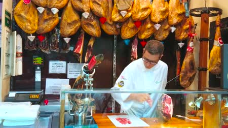 bakkaliye : MALAGA, SPAIN - SEPTEMBER 26, 2019: Visit gourmet store and watch process of hand-cutting of Jamon Iberico (dry-cured Spanish ham), on September 26 in Malaga Stok Video