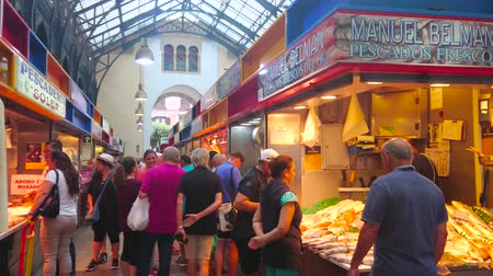 торговый : MALAGA, SPAIN - SEPTEMBER 28, 2019: People walk in fish section of Atarazanas central market, choosing fresh fish and seafood on ice, on September 28 in Malaga Стоковые видеозаписи