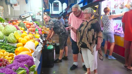 bakkaliye : MALAGA, SPAIN - SEPTEMBER 28, 2019: People choose fresh fruits and vegetables in produce section of Atarazanas central market, on September 28 in Malaga